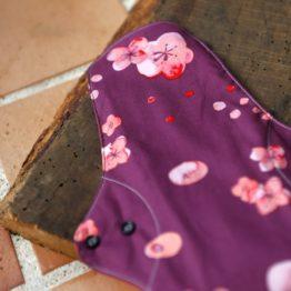 serviette hygiénique lavable Plus avec des motifs de fleurs sur fond mauve de la marque plim vendu par aux retrouvailles.com